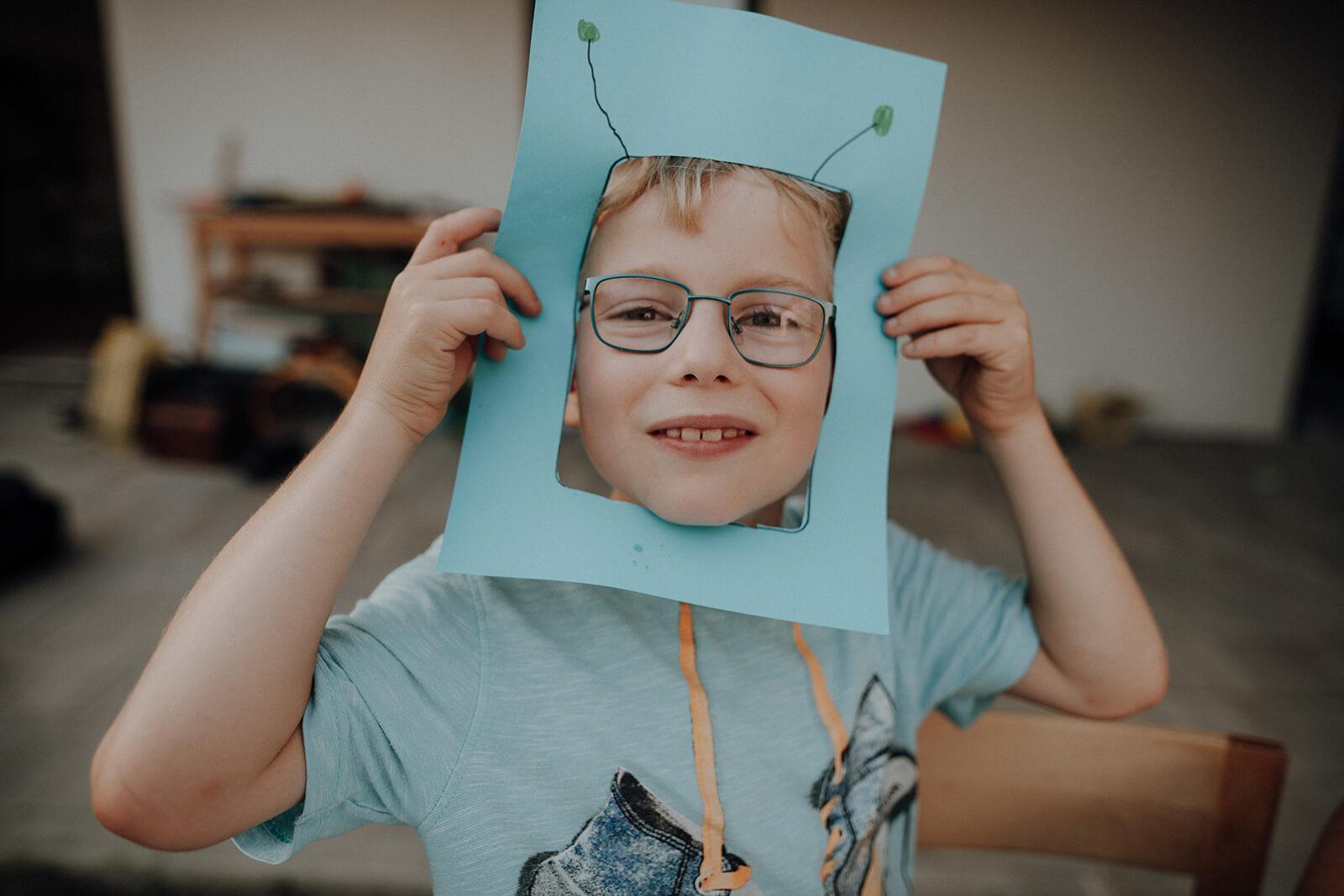 Kind mit selbst gebastelter Maske