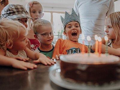 Geburtstagskind bläst Kerzen bei Kinderparty aus