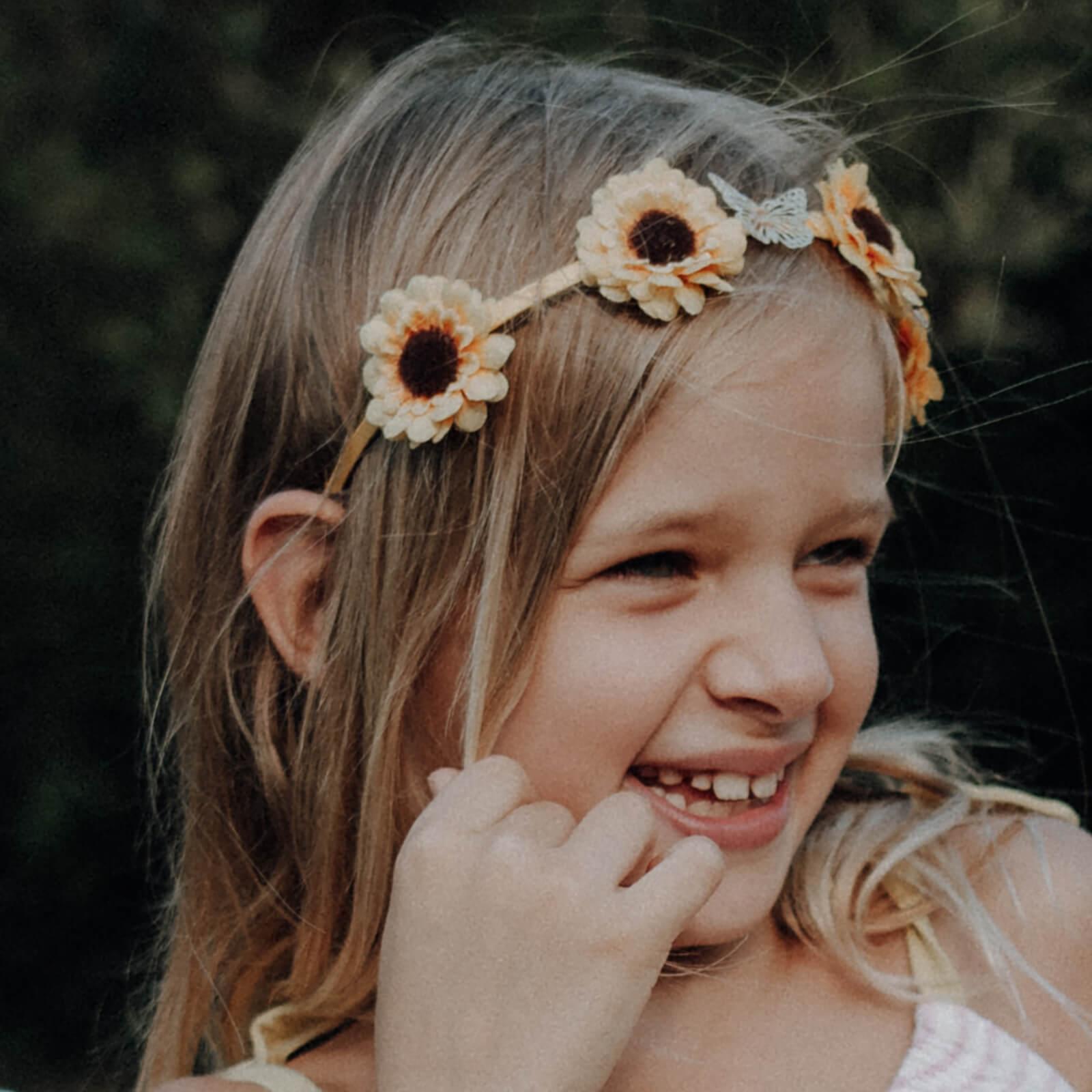Lachendes Kind mit Blumenkranz